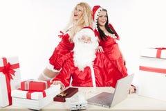 Papá Noel con dos ayudantes atractivos en su oficina Fotos de archivo libres de regalías