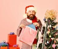 Papá Noel con el árbol de abeto adornado cercano de los paquetes coloridos fotografía de archivo libre de regalías