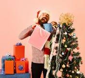 Papá Noel con el árbol de abeto adornado cercano de los paquetes coloridos foto de archivo libre de regalías