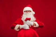 Papá Noel con el bolso grande en fondo del rojo de los vidrios del hombro Foto de archivo