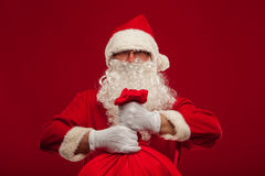 Papá Noel con el bolso grande en fondo del rojo de los vidrios del hombro Imagen de archivo