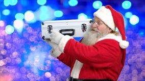 Papá Noel con el caso de plata en fondo azul del bokeh metrajes
