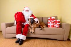 Papá Noel con el perro Fotografía de archivo libre de regalías