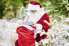 Papá Noel con la caja de regalo y el regalo empaquetan en el bosque nevoso Fotografía de archivo
