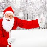 Papá Noel con la tarjeta en blanco Foto de archivo libre de regalías