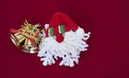 Papá Noel con las campanas de la Navidad del oro en fondo rojo fotografía de archivo