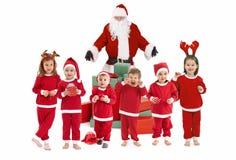 Papá Noel con los pequeños niños felices en traje Imagenes de archivo