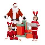 Papá Noel con los pequeños niños felices en traje Imagen de archivo libre de regalías