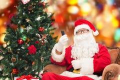 Papá Noel con smartphone y el árbol de navidad Foto de archivo libre de regalías