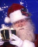 Papá Noel con un presente foto de archivo