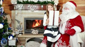 Papá Noel da el regalo de la muchacha, niño sonriente feliz, deseos viene Año Nuevo verdadero, y celebración de la Navidad almacen de metraje de vídeo