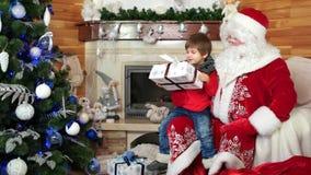 Papá Noel da a muchacho el presente grande, deseos viene niño verdadero, feliz que abraza al santo Nicolás, regalo para el niño metrajes