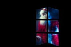 Papá Noel detrás de la puerta de cristal Imagen de archivo libre de regalías
