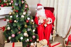 Papá Noel en la butaca cerca de la chimenea Fotografía de archivo libre de regalías