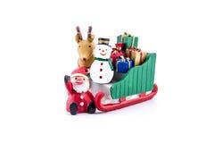 Papá Noel en llevar del trineo regalos con el reno y el muñeco de nieve Imagenes de archivo