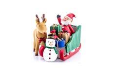 Papá Noel en llevar del trineo regalos con el reno y el muñeco de nieve Imagen de archivo libre de regalías