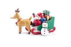 Papá Noel en llevar del trineo regalos con el reno y el muñeco de nieve Fotografía de archivo