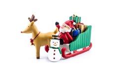 Papá Noel en llevar del trineo regalos con el reno y el muñeco de nieve Fotografía de archivo libre de regalías