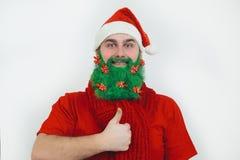 Papá Noel en ropa roja con la barba verde sonríe Foto de archivo libre de regalías