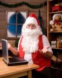 Papá Noel en taller con la computadora portátil Imagen de archivo libre de regalías