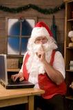 Papá Noel en taller usando la computadora portátil Fotografía de archivo libre de regalías