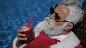Papá Noel feliz goza el beber cerca de la piscina almacen de metraje de vídeo