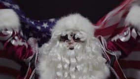 Papá Noel feliz que agita una bandera contra fondo negro - el concepto de los E.E.U.U. de la Navidad o del Día de la Independenci metrajes