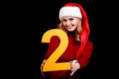 Papá Noel femenino lindo en un casquillo rojo, llevando a cabo el número dos en un fondo negro concepto del día de fiesta de 2018 Fotos de archivo