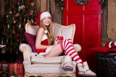 Papá Noel hermoso, atractivo femenino divirtiéndose y sonriendo cerca del árbol de navidad, sentándose en silla del vintage Año N Foto de archivo
