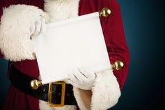 Papá Noel: Llevar a cabo una lista en blanco de la voluta Imagenes de archivo
