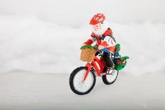 Papá Noel miniatura en la bici imagen de archivo libre de regalías