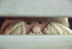 Papá Noel ocultado detrás de una silla imágenes de archivo libres de regalías