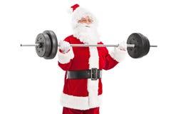 Papá Noel que ejercita con un barbell pesado Imagen de archivo