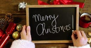 Papá Noel que escribe Feliz Navidad en pizarra almacen de metraje de vídeo