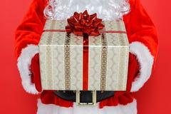 Papá Noel que le da un presente Imagen de archivo libre de regalías