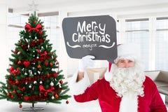 Papá Noel que lleva a cabo el cartel de la forma de la burbuja del pensamiento con el saludo de la Navidad Foto de archivo