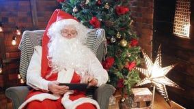 Papá Noel que mira la tableta almacen de metraje de vídeo