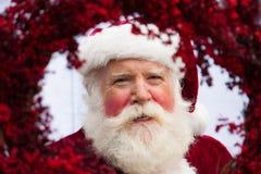 Papá Noel que mira a través de la guirnalda roja Imagenes de archivo