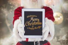 Papá Noel que muestra el saludo de la Navidad y del Año Nuevo en la pantalla digital de la tableta imagen de archivo