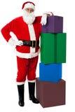 Papá Noel que presenta al lado de la pila de regalos Imagen de archivo