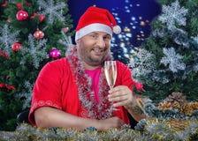 Papá Noel que presenta con el vidrio de vino en fondo de la Navidad Fotografía de archivo