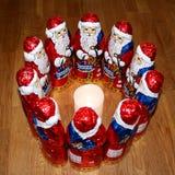 Papá Noel que se coloca alrededor de una vela en el centro Foto de archivo