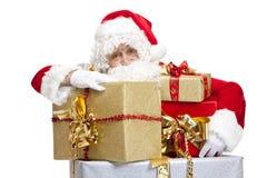 Papá Noel que se inclina en los rectángulos de regalo de la Navidad Fotografía de archivo