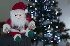 Papá Noel que se sienta al lado del árbol de navidad imágenes de archivo libres de regalías