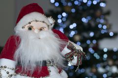 Papá Noel que se sienta al lado del árbol de navidad fotografía de archivo
