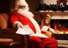 Papá Noel que se sienta en el árbol de navidad, llevando a cabo letras de la Navidad y mirando la cámara Foto de archivo libre de regalías
