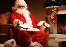 Papá Noel que se sienta en el árbol de navidad, llevando a cabo letras de la Navidad y mirando la cámara Fotos de archivo