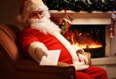 Papá Noel que se sienta en el árbol de navidad, llevando a cabo letras de la Navidad y mirando la cámara Fotos de archivo libres de regalías