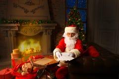 Papá Noel que se sienta en el árbol de navidad, llevando a cabo letras de la Navidad y teniendo un resto por la chimenea Fotos de archivo libres de regalías