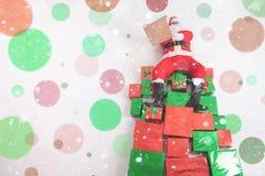 Papá Noel que se sienta en las cajas de regalo grandes y que lee el list d'envie Fotografía de archivo libre de regalías
